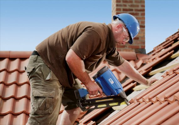 Dachdecker befestigt Dachziegel