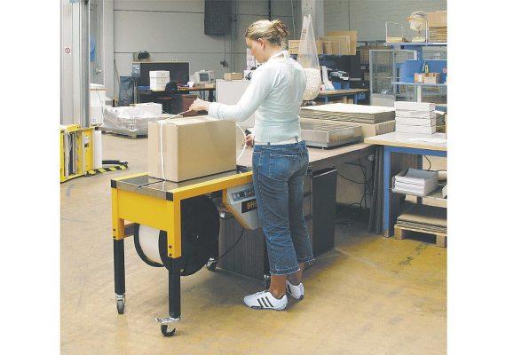 Frau umreift Karton mit Strapex SMA 20