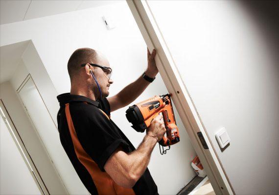 Mann befestigt Rahmen mit Druckluftnagler