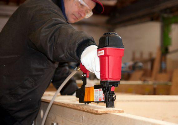 Mann befestigt Holz mit Druckluftnagler