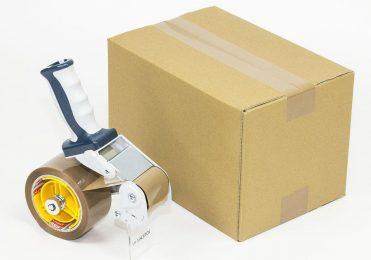 Packband Abroller neben Karton