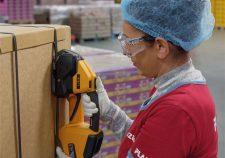 Frau umreift PP-Band am Karton mit Akku-Umreifungsgerät Strapex STB 71