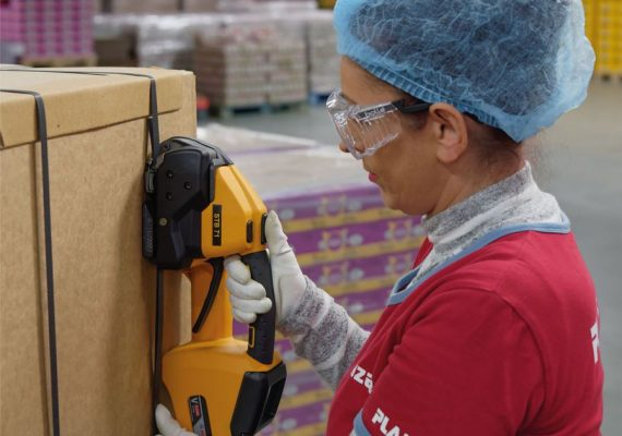 Frau umreift PP-Band am Karton mit Strapex STB 71
