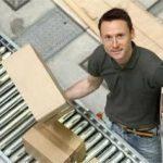 Mann am Fließband beim Verpacken mit Karton in der Hand